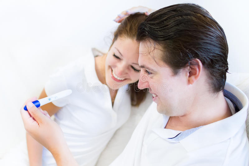 Le couple rit en regardant l'essai enceinte positif image stock