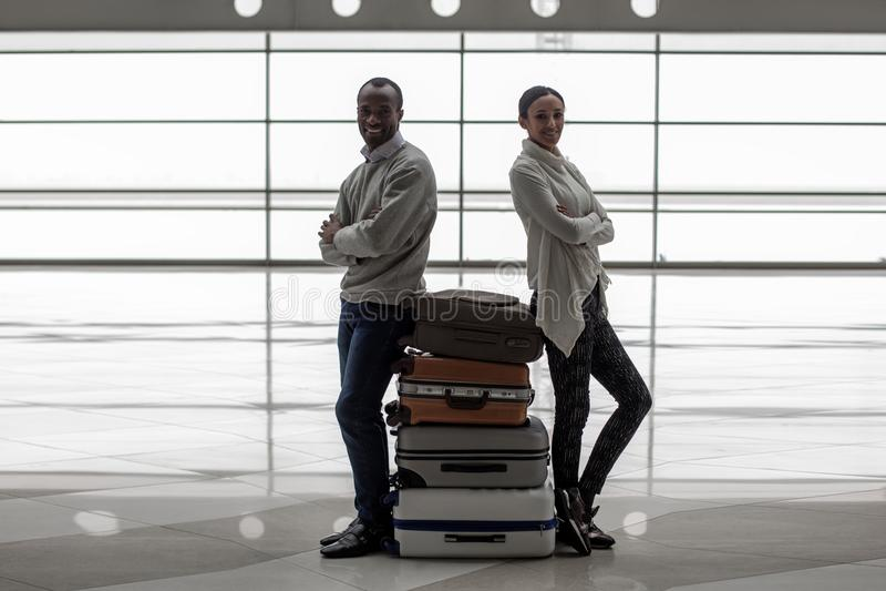 Le couple romantique agréable attend le vol avec des bagages photo libre de droits