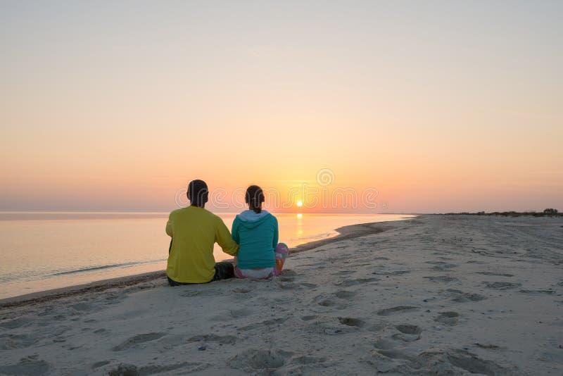 Le couple romantique des voyageurs se repose sur la plage photographie stock