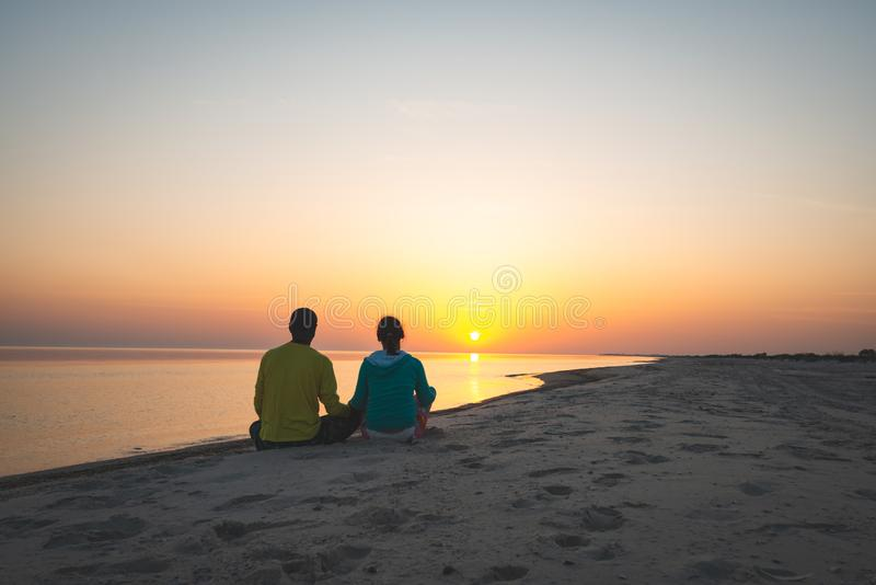 Le couple romantique des voyageurs se repose sur la plage image libre de droits