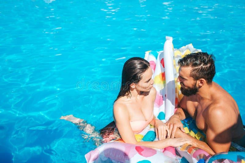 Le couple s'élève dans la piscine et le regard à l'un l'autre Ils sont humides Le couple se penche au matelas d'air photographie stock