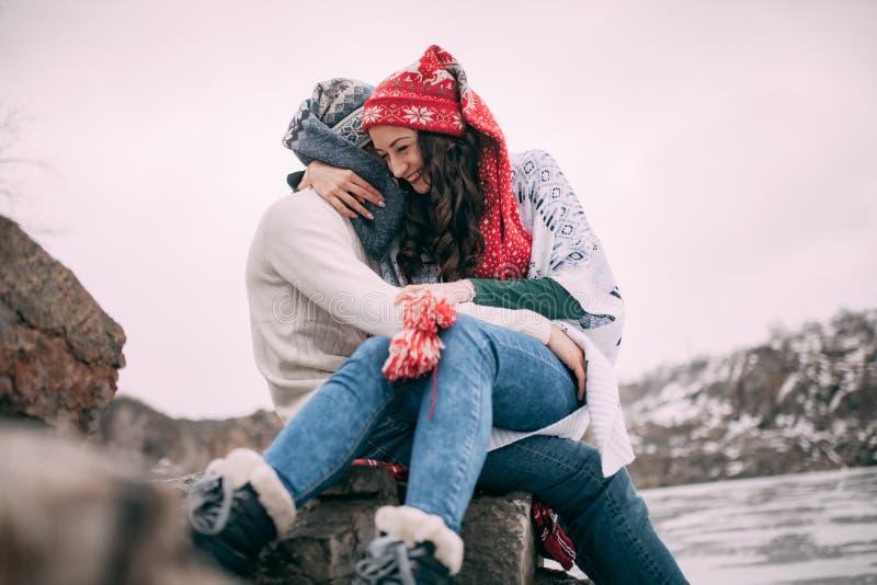Le couple se repose à la roche, embrasse et sourit sur le fond des collines couvertes de neige et du lac congelé closeup photographie stock libre de droits