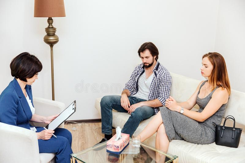 Le couple se repose devant le docteur Ils regardent vers le bas au plancher Le docteur regarde à ses papiers Ils sont image libre de droits
