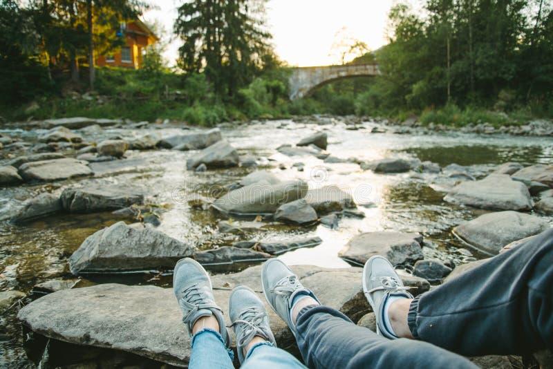 Le couple se repose près de la rivière de montagne et du regard sur le coucher du soleil photographie stock