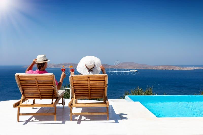 Le couple se repose sur des lits pliants de luxe par la piscine avec des boissons d'apéritif photographie stock