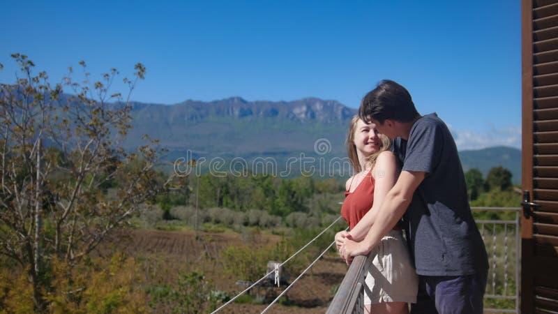 Le couple se tient sur le balcon embrassant et regardant sur l'un l'autre photo stock