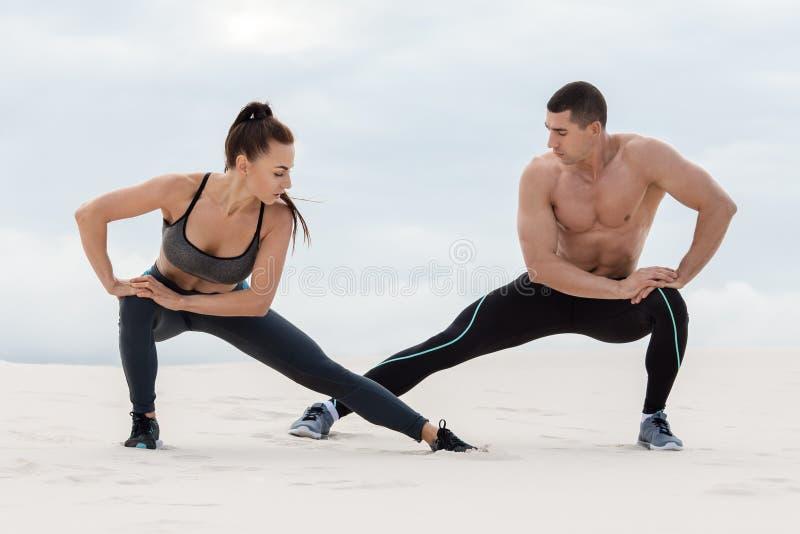 Le couple sportif de forme physique faisant l'étirage s'exerce dehors Beaux homme et femme sportifs photographie stock