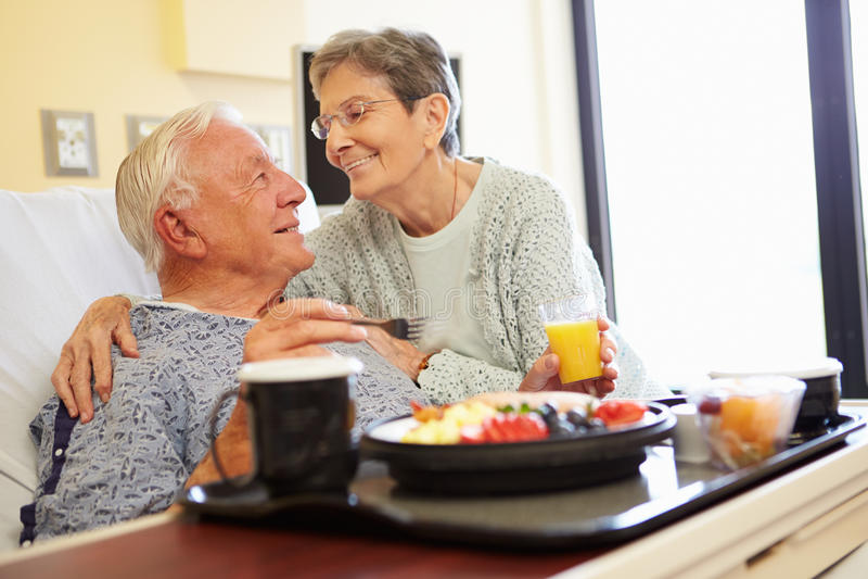 Le couple supérieur dans la chambre d'hôpital en tant que patient masculin prend le déjeuner photo stock
