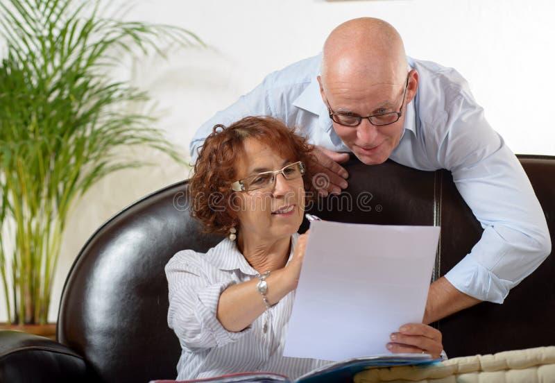 Le couple supérieur regarde un document image stock