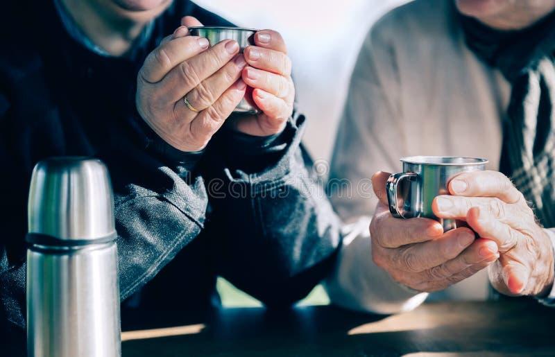 Le couple supérieur remet tenir des tasses avec du café chaud photographie stock