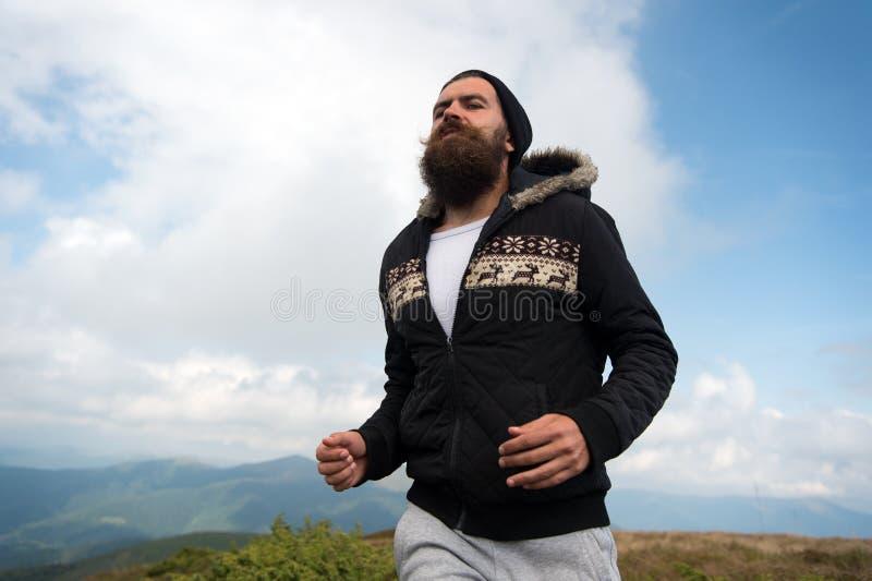 Le coureur d'homme avec la longue barbe fonctionnent sur le paysage de montagne image stock