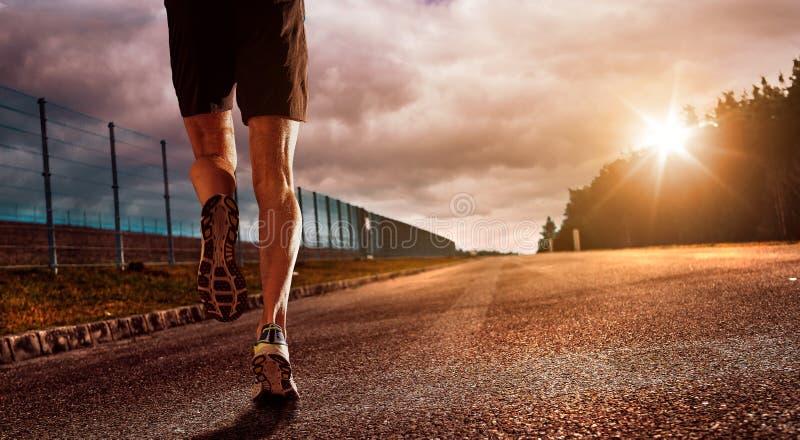 Le coureur dans le coucher du soleil et le succès images stock