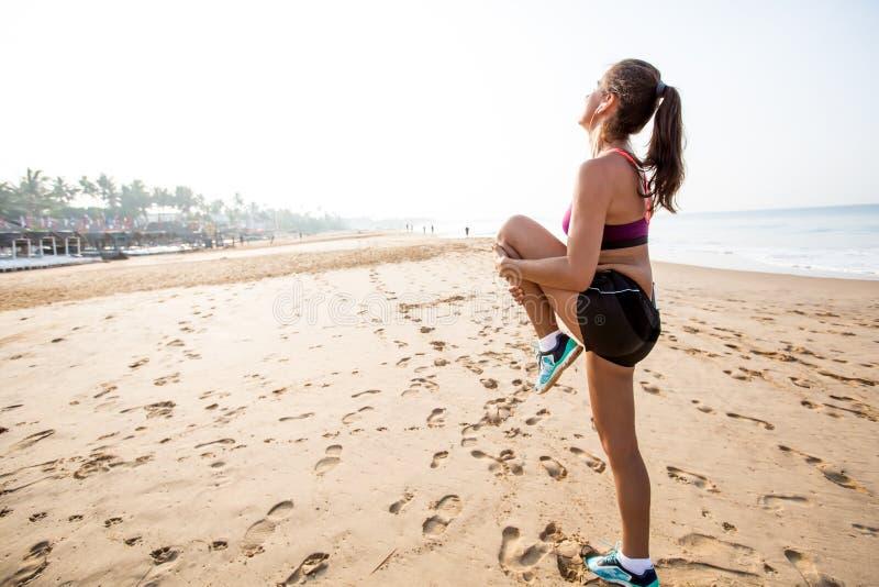 Le coureur de femme étirant des jambes muscles sur la plage au lever de soleil photos stock