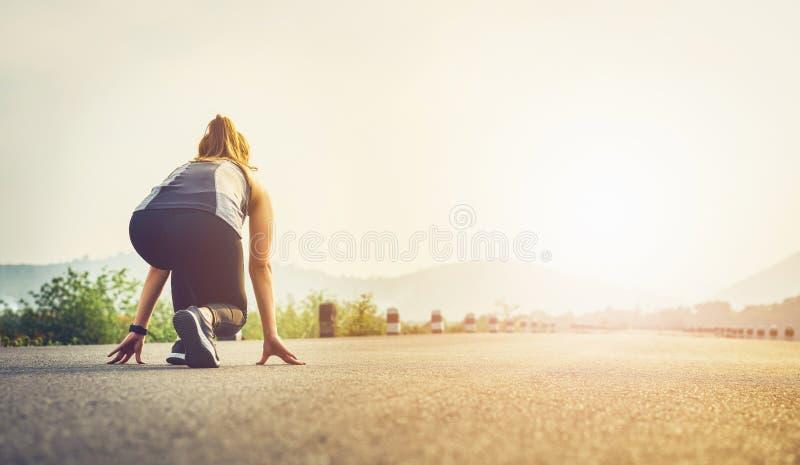 Le coureur de femme sur les chaussures de route sont préparés partir du point de départ o image stock
