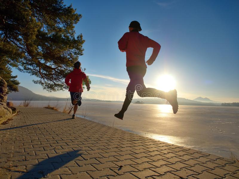 Le coureur de matin avec des sports portent la h?te en parc de lac de ville image stock