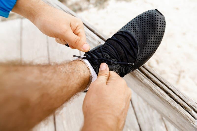 Le coureur lace ses chaussures et prépare à pulser photo stock