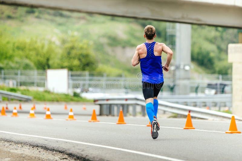 Le coureur masculin dans la compression cogne le fonctionnement dans la route avec la sécurité de cônes du trafic photo stock
