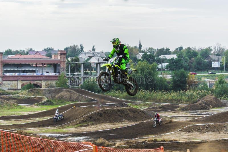 Le coureur sur une moto participe à une course de motocross, saute sur un tremplin photos libres de droits