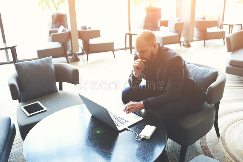 Le courtier masculin réfléchi examine des documents d'assurance sur l'ordinateur portable images libres de droits