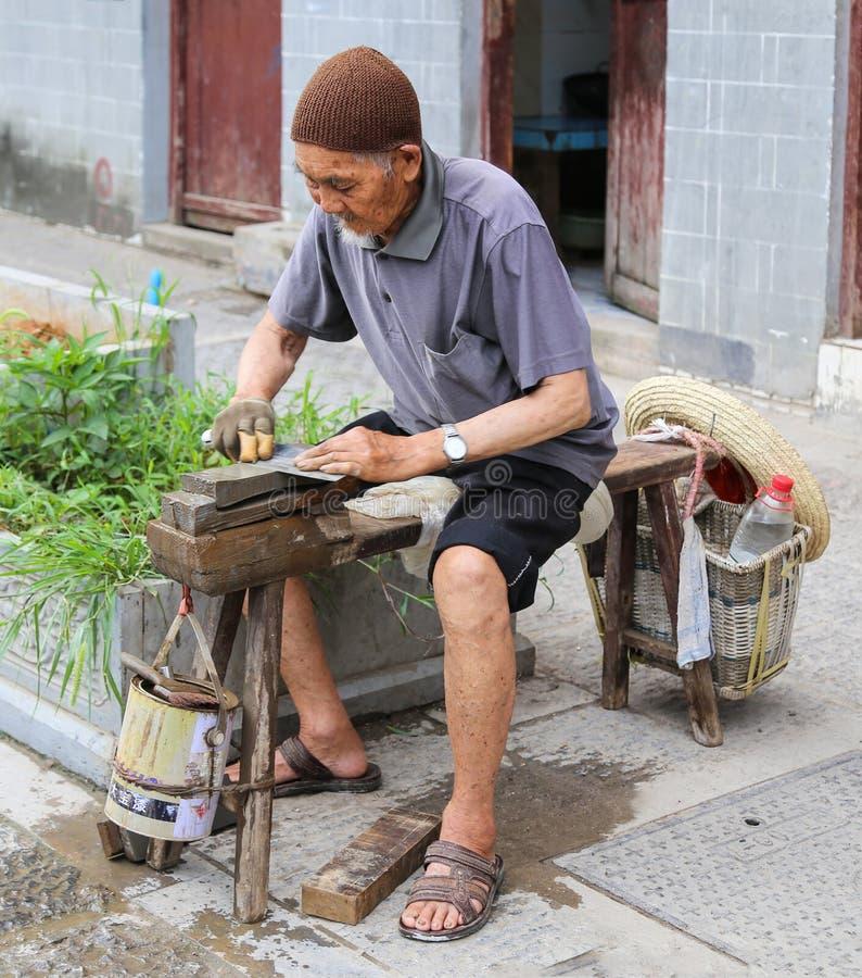 Le couteau de meulage de vieil homme dans la ville antique zhenyuan, Guizhou, porcelaine photographie stock libre de droits