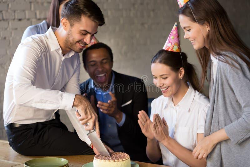 Le couteau de participation de gar?on d'anniversaire a coup? le g?teau pr?sent? par des coll?gues photo libre de droits
