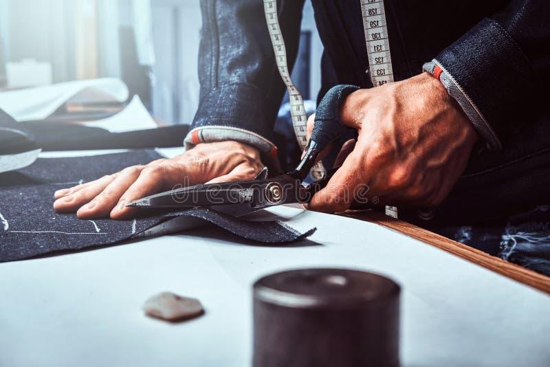 Le couturier d?coupe le tissu avec des ciseaux photos libres de droits