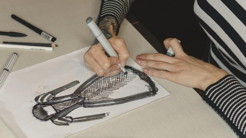 Le couturier de fille dessine la robe de soirée de croquis photo stock