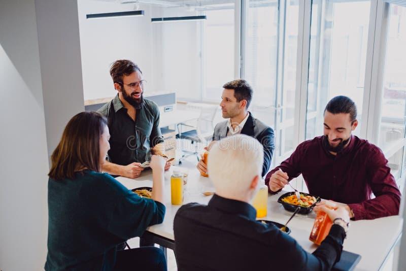 Le coworkers som äter på tabellen i kontoret fotografering för bildbyråer