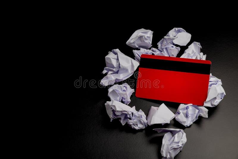 Le crédit/débit rouge/carte de achat est dans le papier chiffonné sur le fond/table noirs N'achetez rien jour images libres de droits