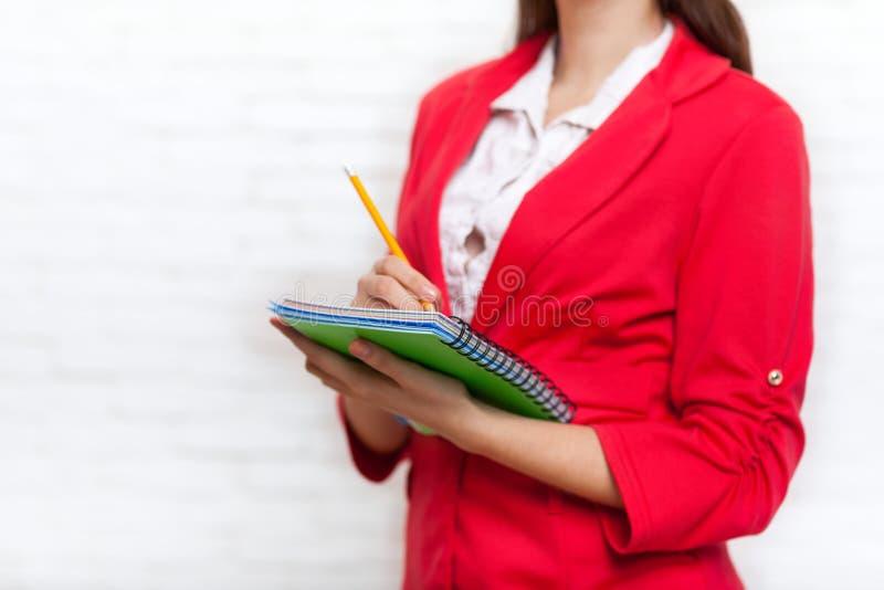 Le crayon de carnet de prise de femme d'affaires écrivent la veste de rouge d'usage photos libres de droits