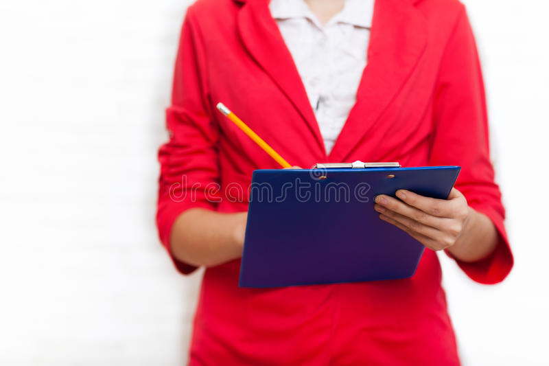 Le crayon de dossier de prise de femme d'affaires écrivent la veste de rouge d'usage image stock
