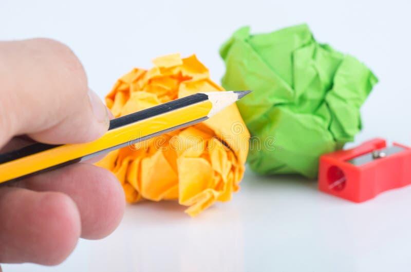 Le crayon de participation de main, chiffonnent le papier et l'affûteuse au-dessus du fond blanc photographie stock
