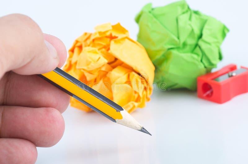 Le crayon de participation de main, chiffonnent le papier et l'aff?teuse au-dessus du fond blanc image libre de droits