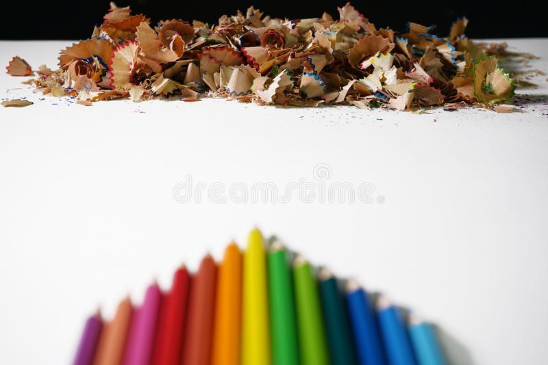 Le crayon en bois coloré empilé pour l'affûteuse d'utiliser-et a coloré des crayons sur le livre blanc photo libre de droits
