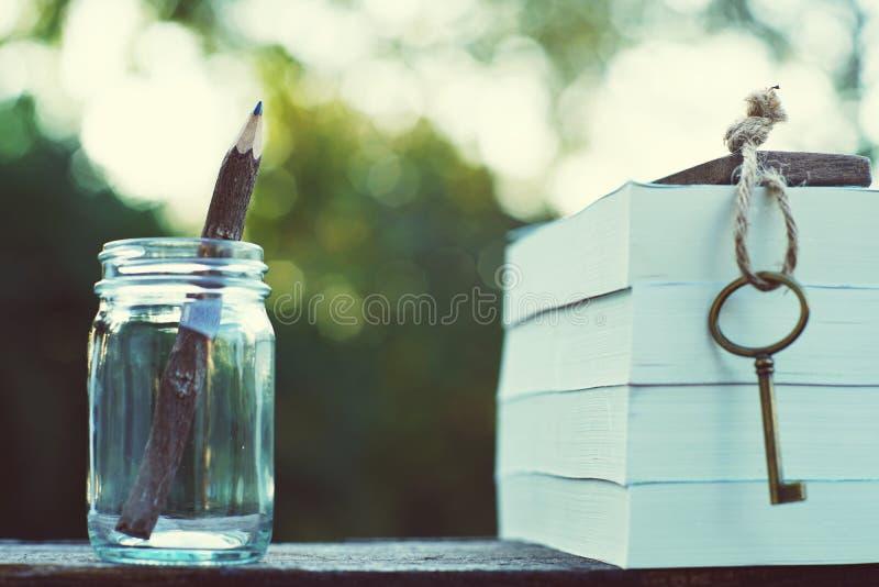 Le crayon a fait du bois dans la bouteille en verre, la clé de cru et la pile de livre sur la table en bois avec la lumière de ma photo stock