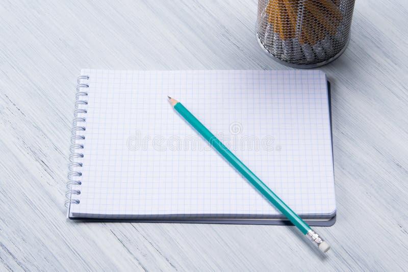Le crayon pointu simple se trouve sur un bloc - notes vide images stock