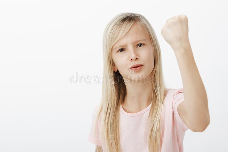 Le creceré y mostraré Retrato del niño femenino enojado descontentado con el pelo rubio, aumentando el puño apretado y la sacudid imagenes de archivo
