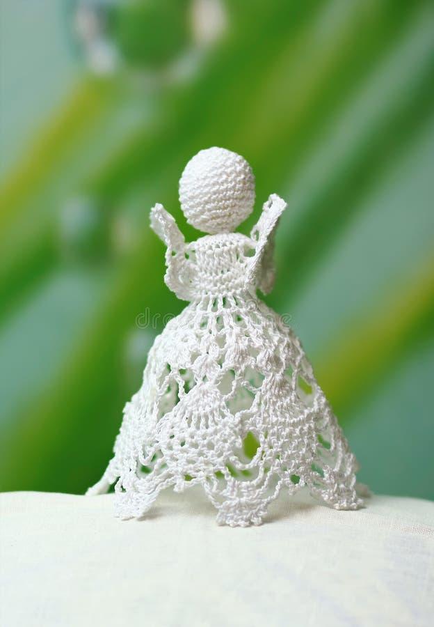 Le crochet authentique traditionnel a tricoté l'ange blanc de dentelle sur le fond vert, décor de Pâques image libre de droits