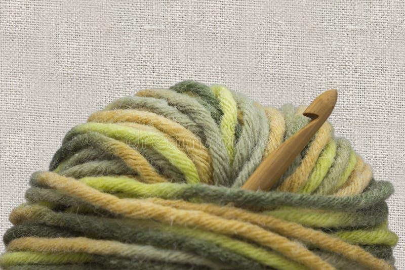 Le crochet de crochet en bambou naturel en bois, la boule verte de laine de fil et le crochet entourent la photo sur le fond de t images stock