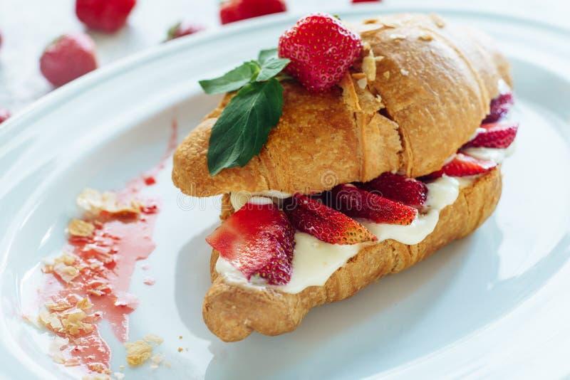 Le croissant doux a coupé deux avec de la crème et la fraise images stock