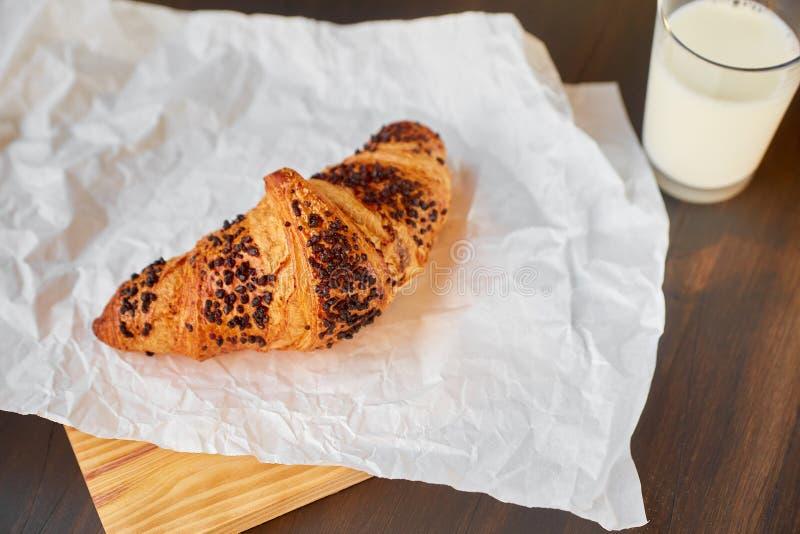 Le croissant frais sur le blanc a chiffonné le papier et un conseil en bois avec un verre de lait Croissant fraîchement cuit au f images stock