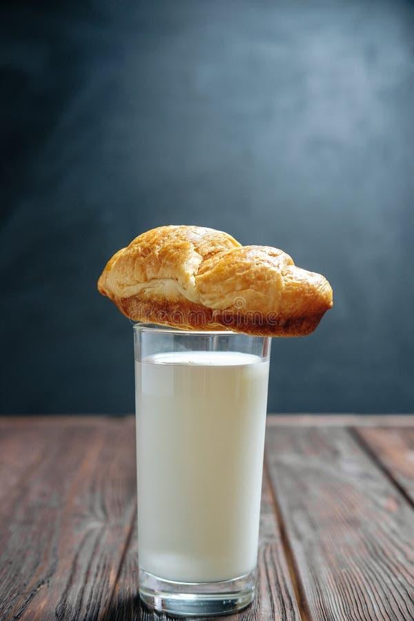 Le croissant se trouve sur le verre de lait sur la table foncée en bois photos libres de droits