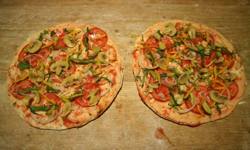 Le croste della pizza hanno completato con i pomodori ed i funghi prima di cuocere immagini stock libere da diritti