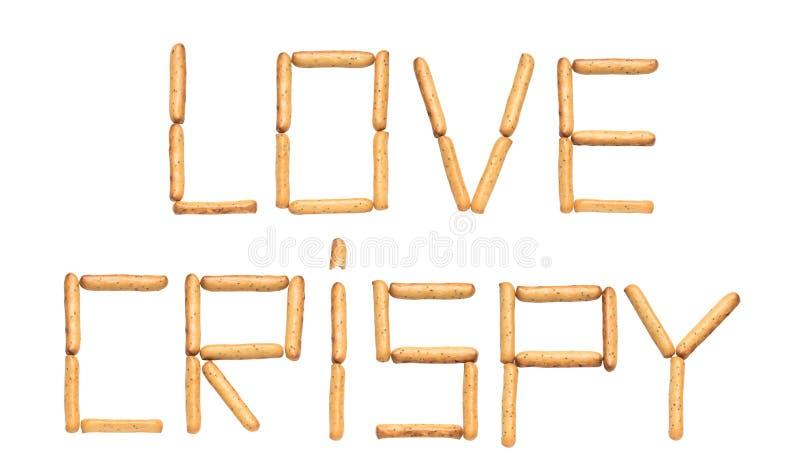 Le croustillant d'amour de mot composé par des batons de pain avec des clous de girofle sur un fond blanc images stock