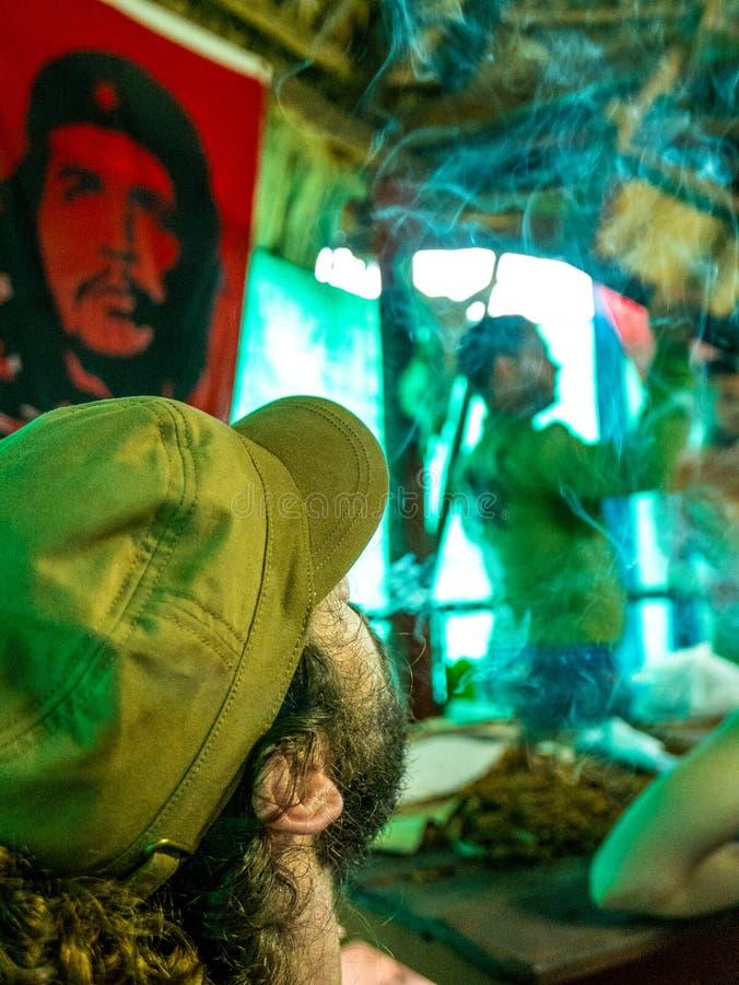Le CUBA, juin 2016 : jeune homme avec les cigares de barbe et d'un chapeau militaire et la fumée de tabagisme d'émission, à la pl photos libres de droits