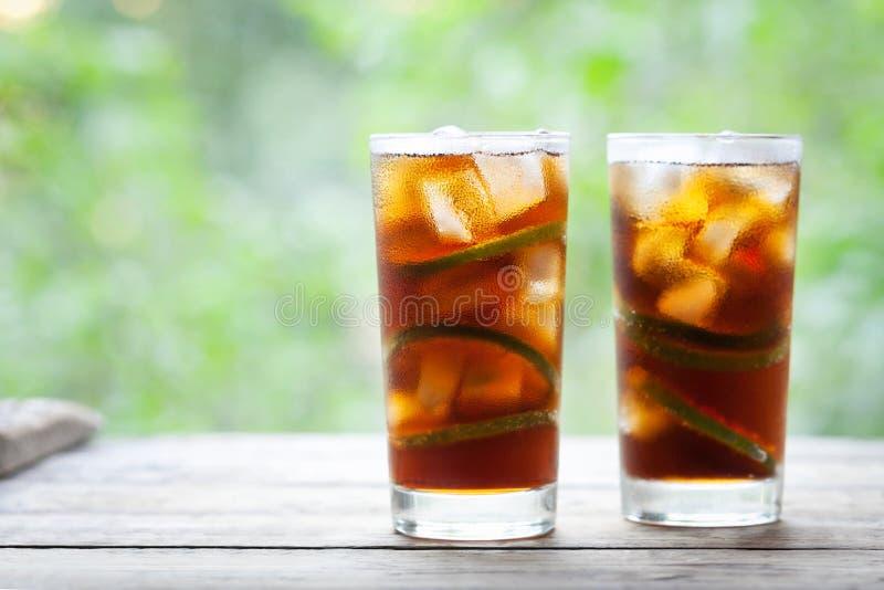 Le Cuba Libre ou Long Island a glacé le cocktail de thé avec les boissons fortes, le kola, la chaux et la glace en verre, le long photos stock
