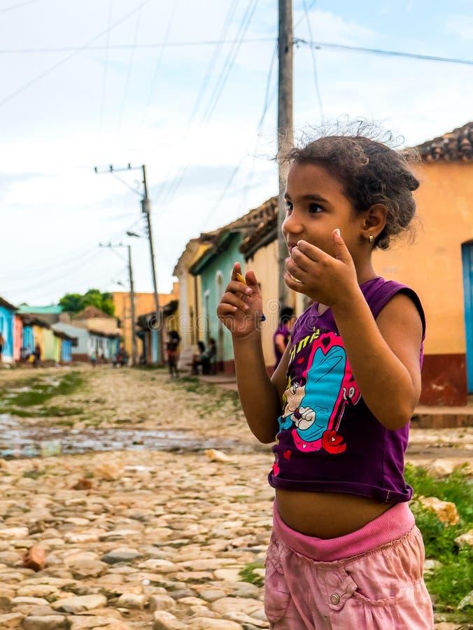 Le Cuba, Trinidad Juin 2016 : badinez la fille jouant avec le crayon sur la rue, sur le côté le plus pauvre de la ville image libre de droits