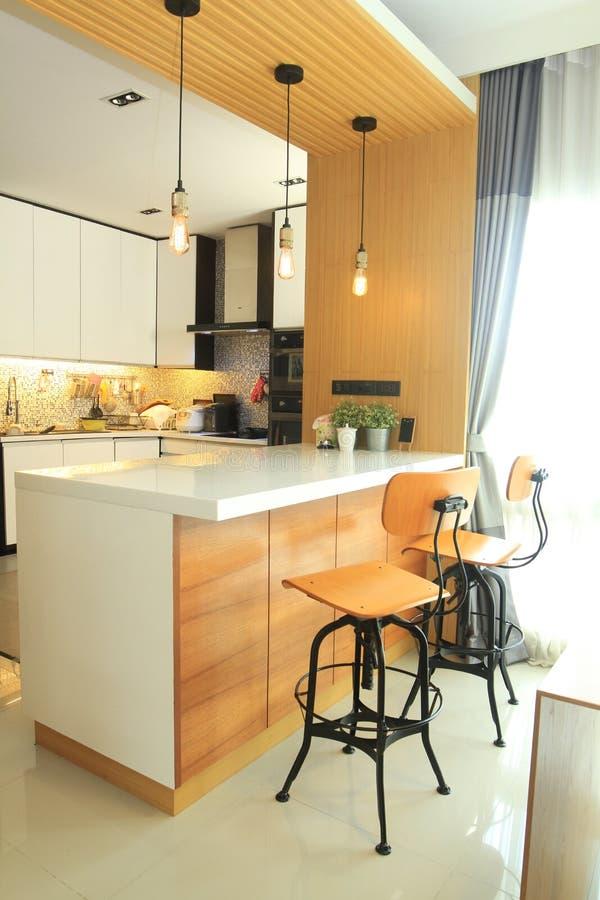Le cucine e le isole di interior design sono collegate dall'area pranzante fotografia stock libera da diritti