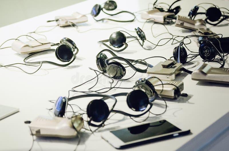 Le cuffie, cuffia avricolare, telefoni sono sulla tavola immagini stock libere da diritti