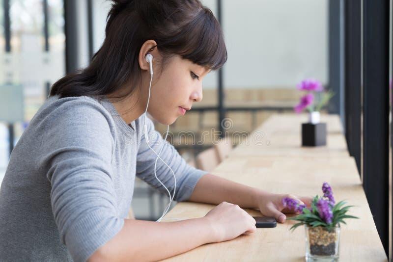 le cuffie d'uso della ragazza dello studente femminile asiatico dell'adolescente ed ascoltano immagini stock libere da diritti